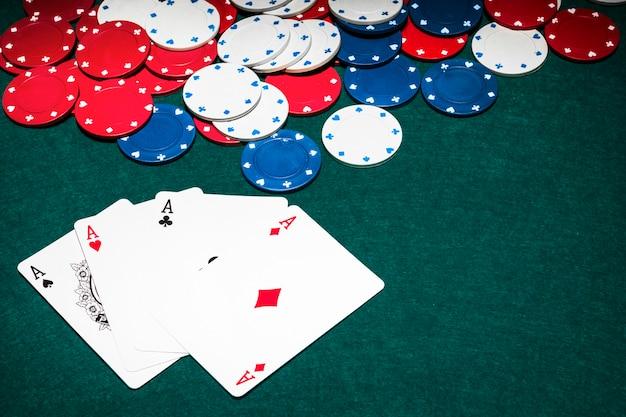 Scheda di tre assi e fiches del casinò sul tavolo da poker