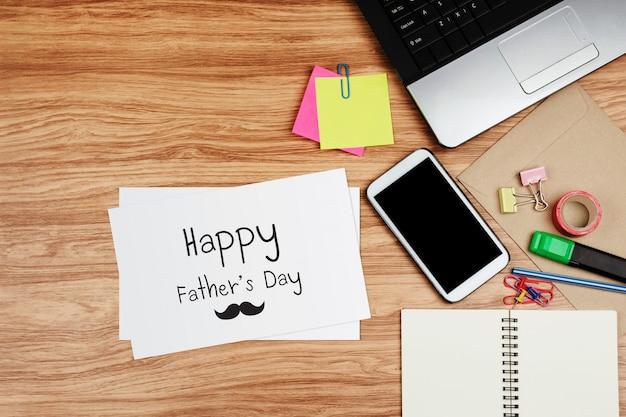 Scheda felice di festa del papà con gli articoli per ufficio sullo scrittorio di legno