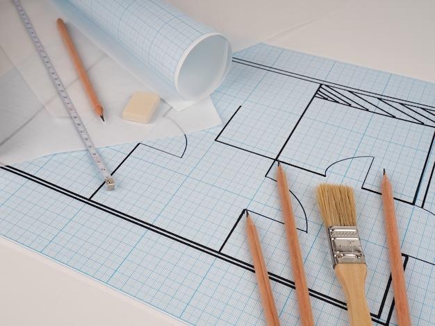 Schema schematico dell'appartamento, disegno su carta millimetrata in un rotolo, vicino al pennello concetto di costruttore di riparazione e design. pianta della casa, alloggio accogliente, costruzione di edifici, nuova costruzione