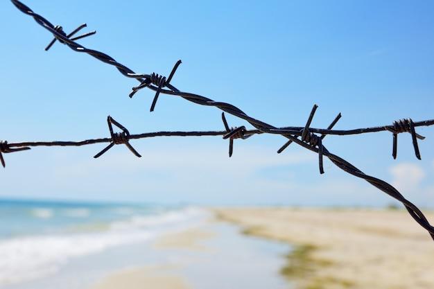 Scherma della riva del mare con filo di ferro spinato