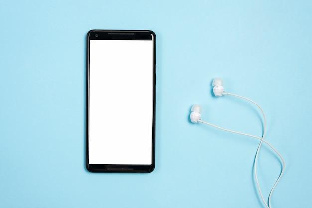 Schermo bianco bianco display sul cellulare con auricolari su sfondo blu