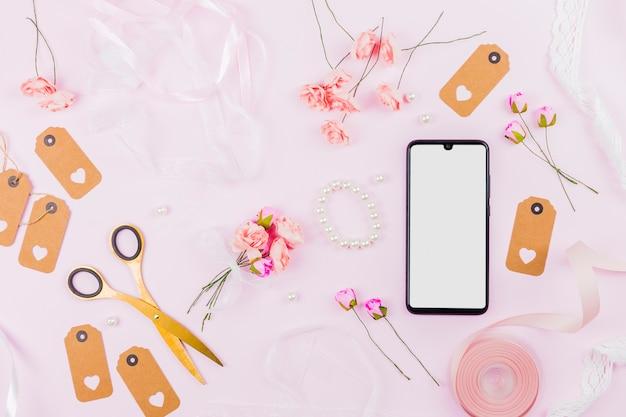 Schermo bianco con telefono cellulare con nastri; rose; tag e perla su sfondo rosa
