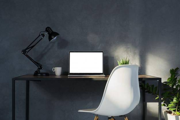 Schermo bianco del computer portatile sull'area di lavoro