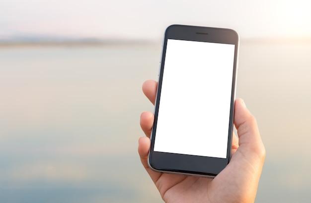 Schermo bianco del telefono di perforazione della mano allo stile di vita all'aperto