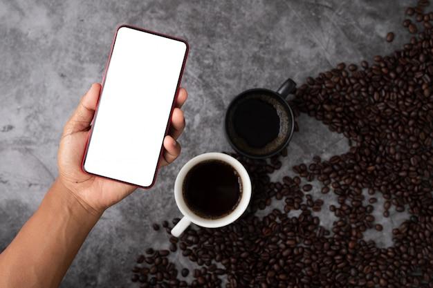 Schermo bianco della stretta umana della mano sullo smart phone, sul telefono cellulare, sulla compressa sulla tazza di caffè nero e sui chicchi di caffè.