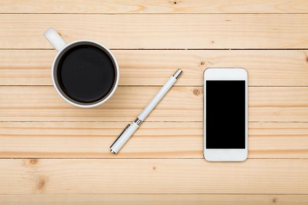 Schermo bianco dello smartphone sulla tavola di legno, vista superiore