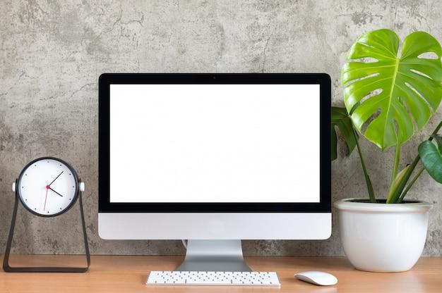 Schermo bianco di tutto in un computer, tastiera, mouse, vaso di piante di monstera e orologio sul tavolo di legno