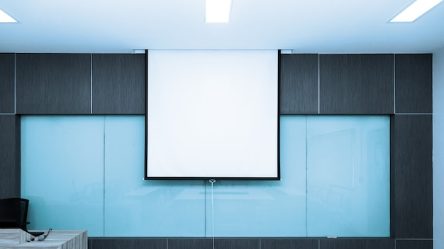 Schermo bianco nella stanza di classe vuota o nella stanza di seminario