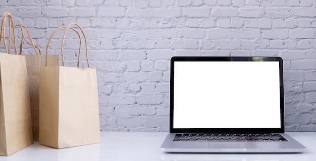 Schermo bianco su laptop, notebook e sacchetti di carta kraft.