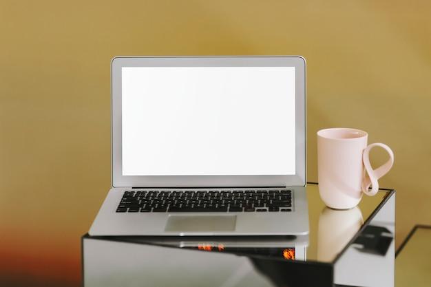 Schermo del computer portatile in bianco e una tazza di caffè rosa