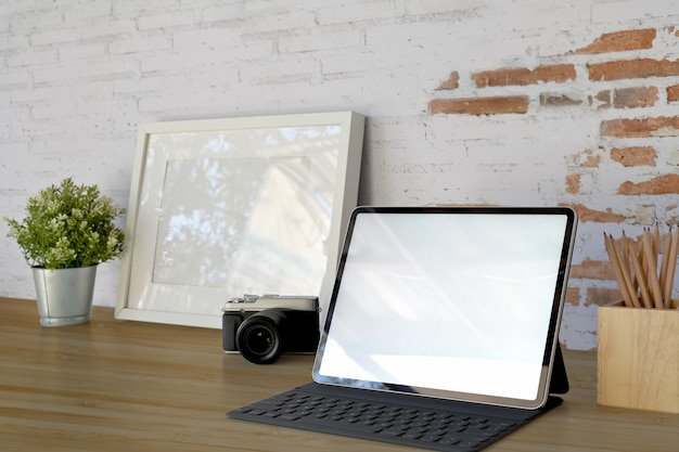 Schermo di computer in bianco della compressa sul posto di lavoro nella parte anteriore sul vecchio muro di mattoni bianco con lo spazio della copia