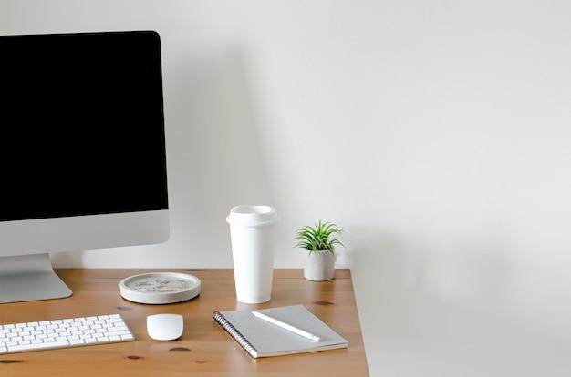 Schermo di personal computer moderno sulla tavola di legno con una tazza di caffè e una pianta aerea di tillandsia