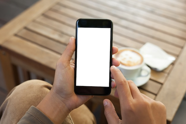 Schermo e dito in bianco mobili del telefono della tenuta della mano del primo piano che tocca nella caffetteria