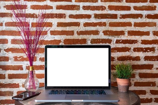 Schermo in bianco del computer portatile con lo smart phone sulla tavola con il muro di mattoni rosso