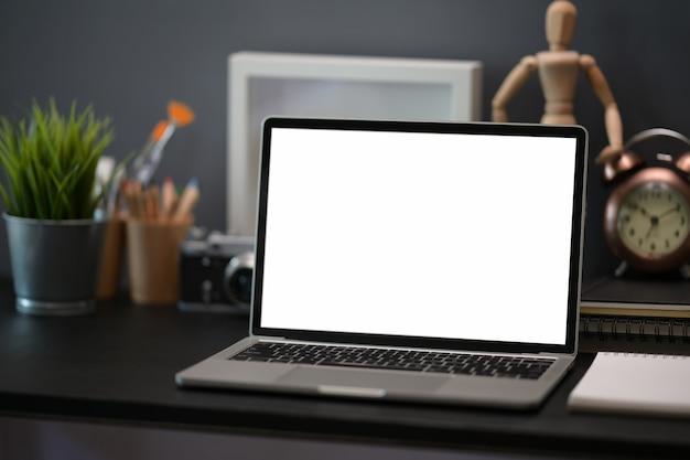 Schermo in bianco del computer portatile sull'area di lavoro di web design