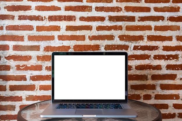 Schermo in bianco del computer portatile sulla tavola con il muro di mattoni rosso