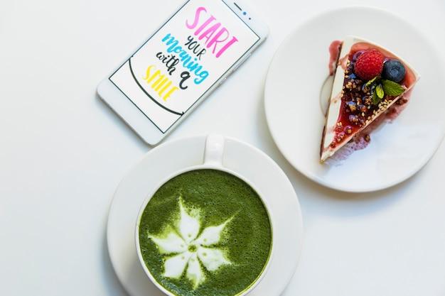 Schermo mobile con messaggio sullo schermo; tazza di tè verde matcha e fetta di torta sul piatto su sfondo bianco