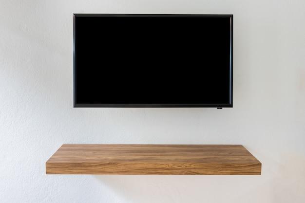 Schermo televisivo nero di led tv sul fondo bianco della parete con la tavola di legno moderna nella sala.