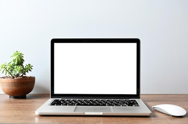 Schermo vuoto moderno computer portatile con mouse, smart phone e succulente sul tavolo di legno in ufficio vista sfondi