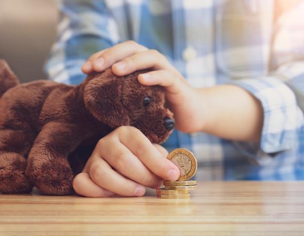 Scherzi la mano che impila e che conta le monete di libbra sulla tavola di legno mentre playin gwith il suo giocattolo del cane, i bambini che imparano circa la responsabilità finanziaria o che progettano il concetto di risparmio.