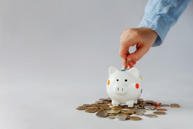 Scherzi la mano che mette la moneta nel porcellino salvadanaio o nel salvadanaio.