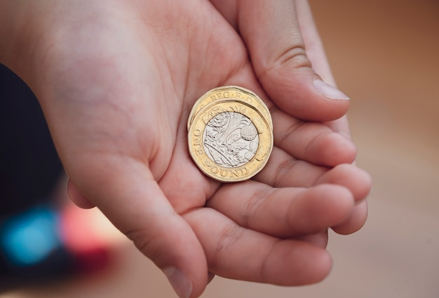 Scherzi la mano che mostra soldi due monete da una libbra sulle sue mani, bambino che tiene una nuova sterlina britannica su entrambe le mani, nuova moneta da una sterlina, 2017 design
