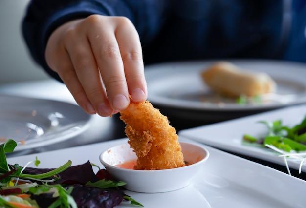 Scherzi la mano che tiene il gambero fritto e l'immersione con salsa cocktail, gamberetti fritti fatti in casa della noce di cocco con salsa dolce, menu dello spuntino per il bambino, cibo asiatico
