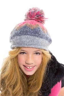 Scherzi la ragazza con la protezione della lana dell'inverno che sorride sul bianco