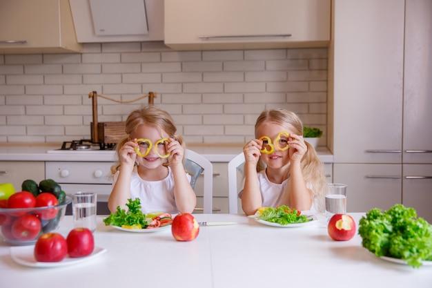 Scherzi la ragazza divertendosi con le verdure dell'alimento alla cucina, i bambini mangiano l'alimento sano nella cucina