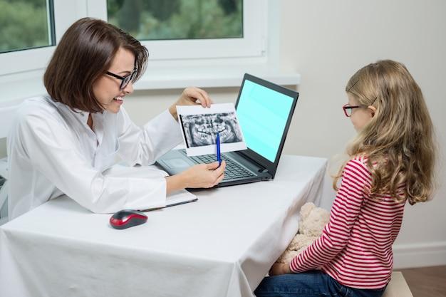 Scherzi la ragazza su consultazione con il dentista, esaminando i raggi x dentali