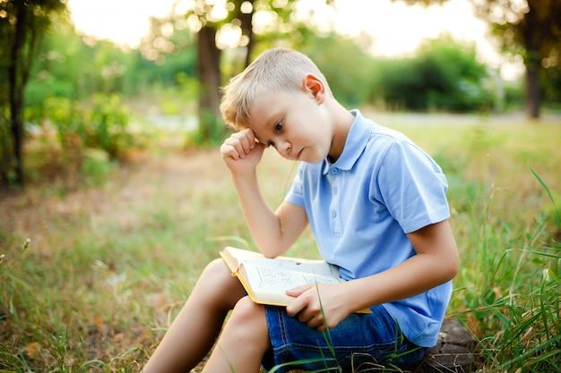 Scherzi la seduta nella foresta con il libro sulle ginocchia.