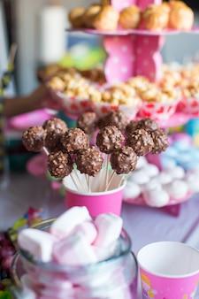 Schiocchi e popcorn della torta di cioccolato sulla tavola del dessert alla festa di compleanno del bambino