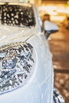 Schiuma del lavaggio della bolla sulla superficie dell'automobile
