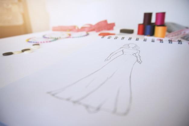 Schizzi di abbigliamento di moda design disegno in atelier. concetto di design creativo