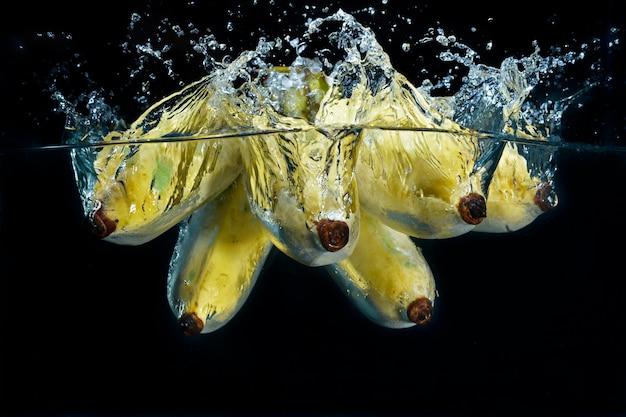 Schizzi di banane in schizzi d'acqua limpida