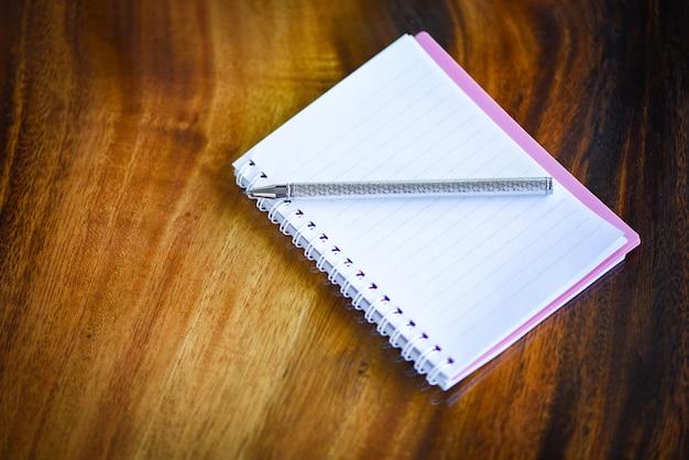 Schizzi il libro con le pagine in bianco della penna o del taccuino su legno. articoli per ufficio di affari della carta del taccuino o concetto di istruzione
