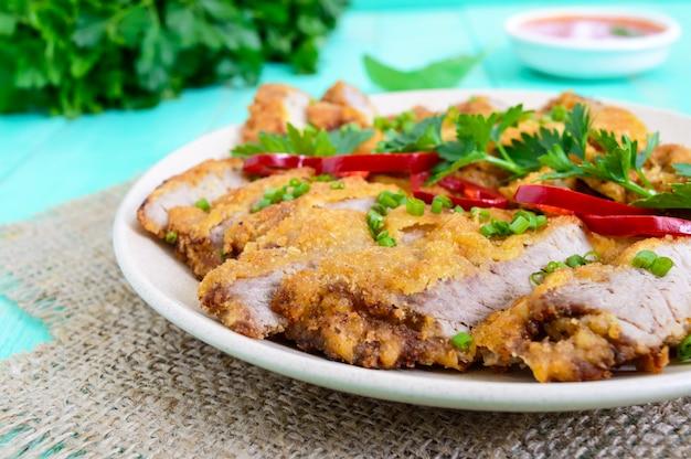 Schnitzel dorato fette tritate e una ciotola di insalata di verdure su un tavolo di legno chiaro. dieta sana. avvicinamento
