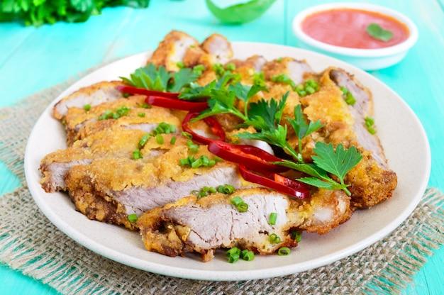 Schnitzel dorato fette tritate e una ciotola di insalata di verdure su un tavolo di legno chiaro. dieta sana.