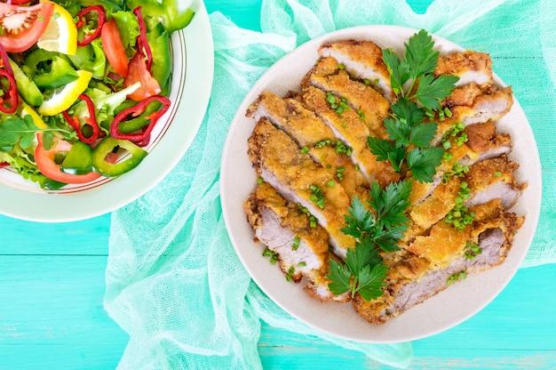 Schnitzel dorato fette tritate e una ciotola di insalata di verdure su un tavolo di legno chiaro. vista dall'alto. dieta sana.