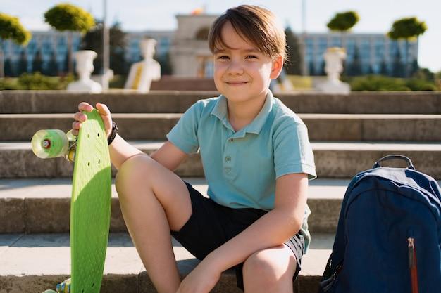School boy in polo blu seduto sulle scale con uno zaino blu e penny verde a bordo