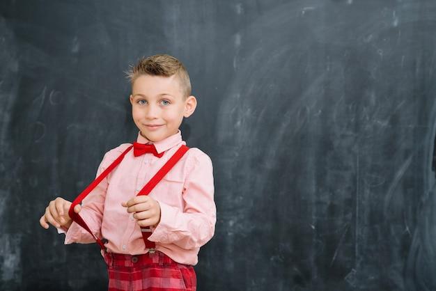 Schoolboy tirando parentesi graffe alla lavagna