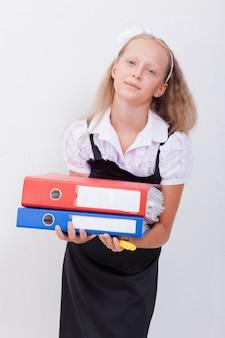 Schoolgirl tenendo la penna e le cartelle nelle sue mani su sfondo bianco