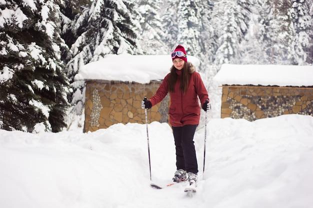 Sci donna nella foresta invernale. allenamento sci sciatore inesperto. giovane sciatore donna caucasica