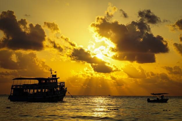 Sciabica e pescatore del peschereccio sull'oceano dell'acqua e cielo drammatico delle nuvole ad alba - mare del peschereccio al tramonto della siluetta di alba