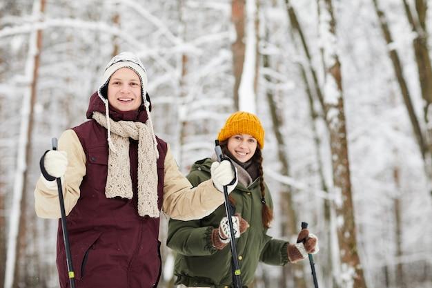 Sciare sorridente delle coppie nella foresta