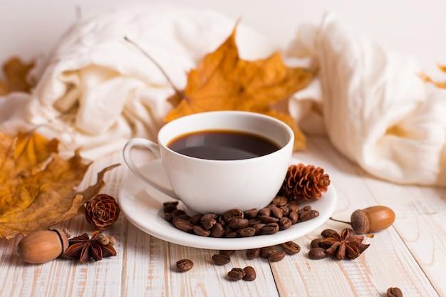 Sciarpa bianca, una tazza di caffè con chicchi di caffè sparsi, foglie gialle secche su un tavolo di legno. mood autunnale, copyspace.