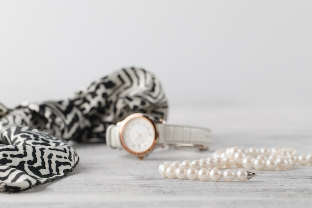 Sciarpa donna sul tavolo con bijouterie di profumo e perla