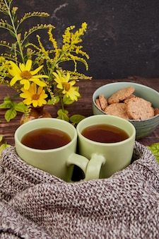 Sciarpa lavorata a maglia con calda tazza di tè.