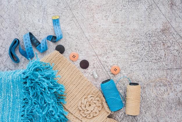 Sciarpa lavorata a maglia; nastro di misurazione; pulsante; bobine su sfondo con texture
