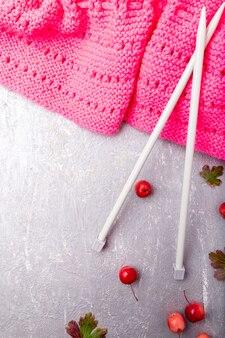 Sciarpa rosa vicino ai ferri da maglia